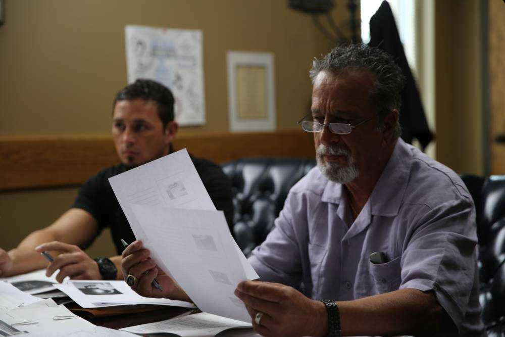 Retired Detective Rhodes Sanchez and Detective Aubrey St. Angelo looking at notes.