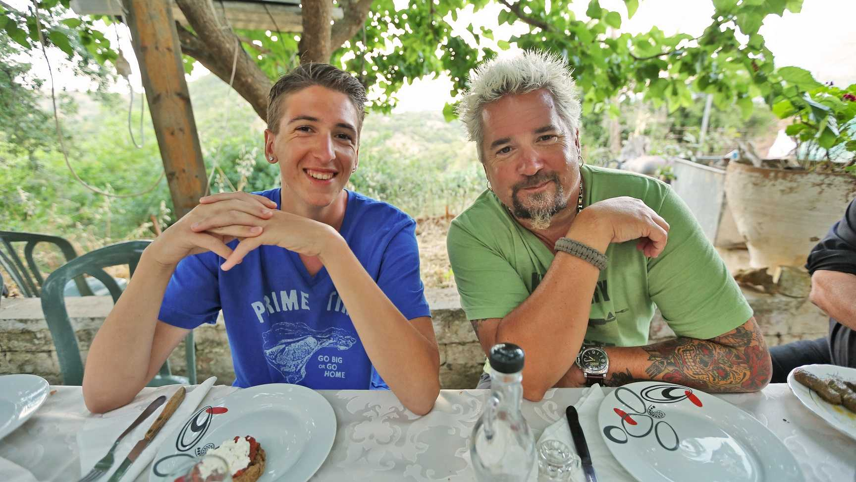 Portrait shot of Guy and Hunter Fieri in Crete,Greece, where they are sitting down for a traditional Greek dinner outside on a terrace, as seen on Food Network's Guy's European Vacation, The Epic Culinary Adventure Special.